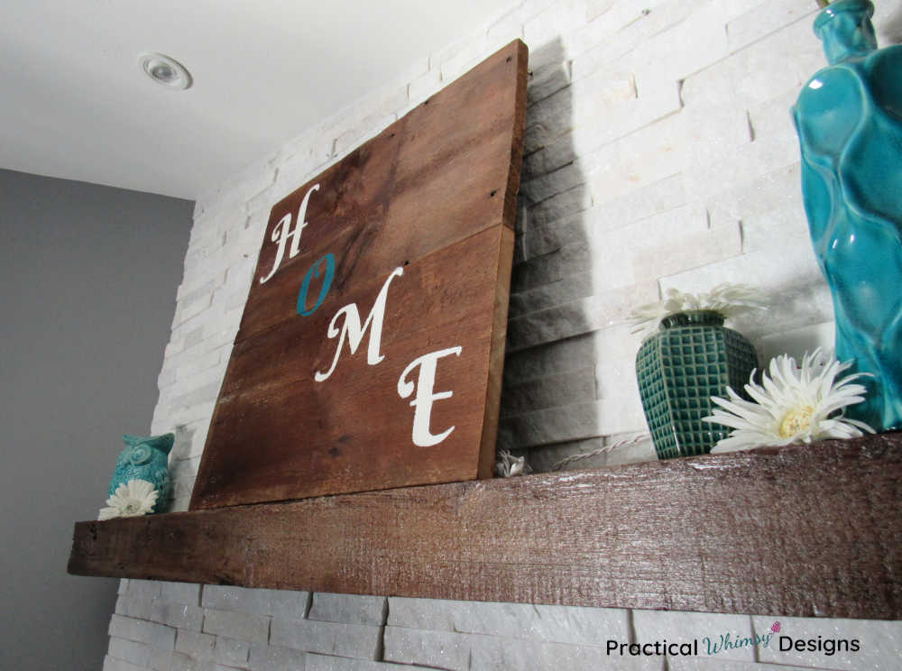 Wooden home sign on mantel with teal vases, white flowers, and teal owl