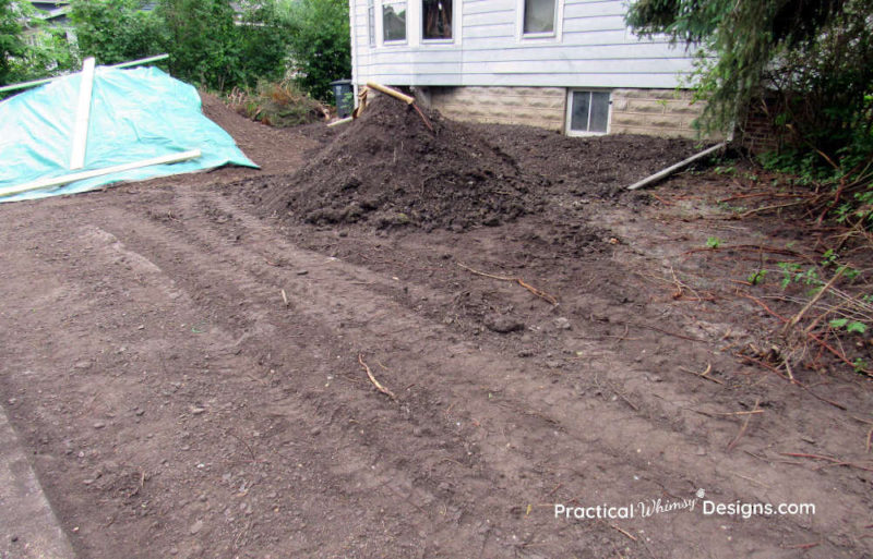 Mounds of dirt in the side yard after excavation